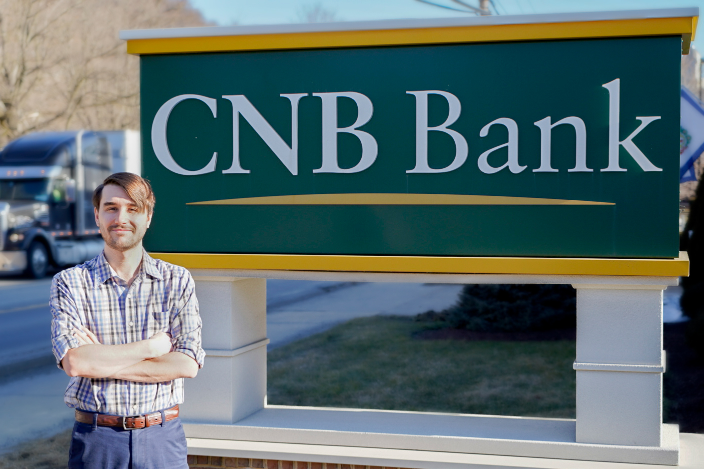 Photo of employee standing in front of CNB Bank sign with arms crossed.